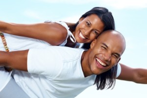 Closeup portrait of a joyful young couple on holiday having fun against sky