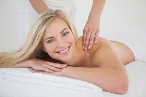 Pretty blonde enjoying a massage smiling at camera